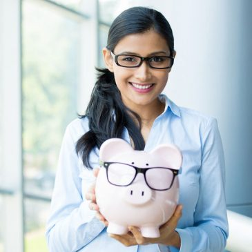 closeup portrait happy, smiling business woman, holding pink piggy bank, wearing big black glasses isolated indoors office background. financial budget savings, smart investment concept