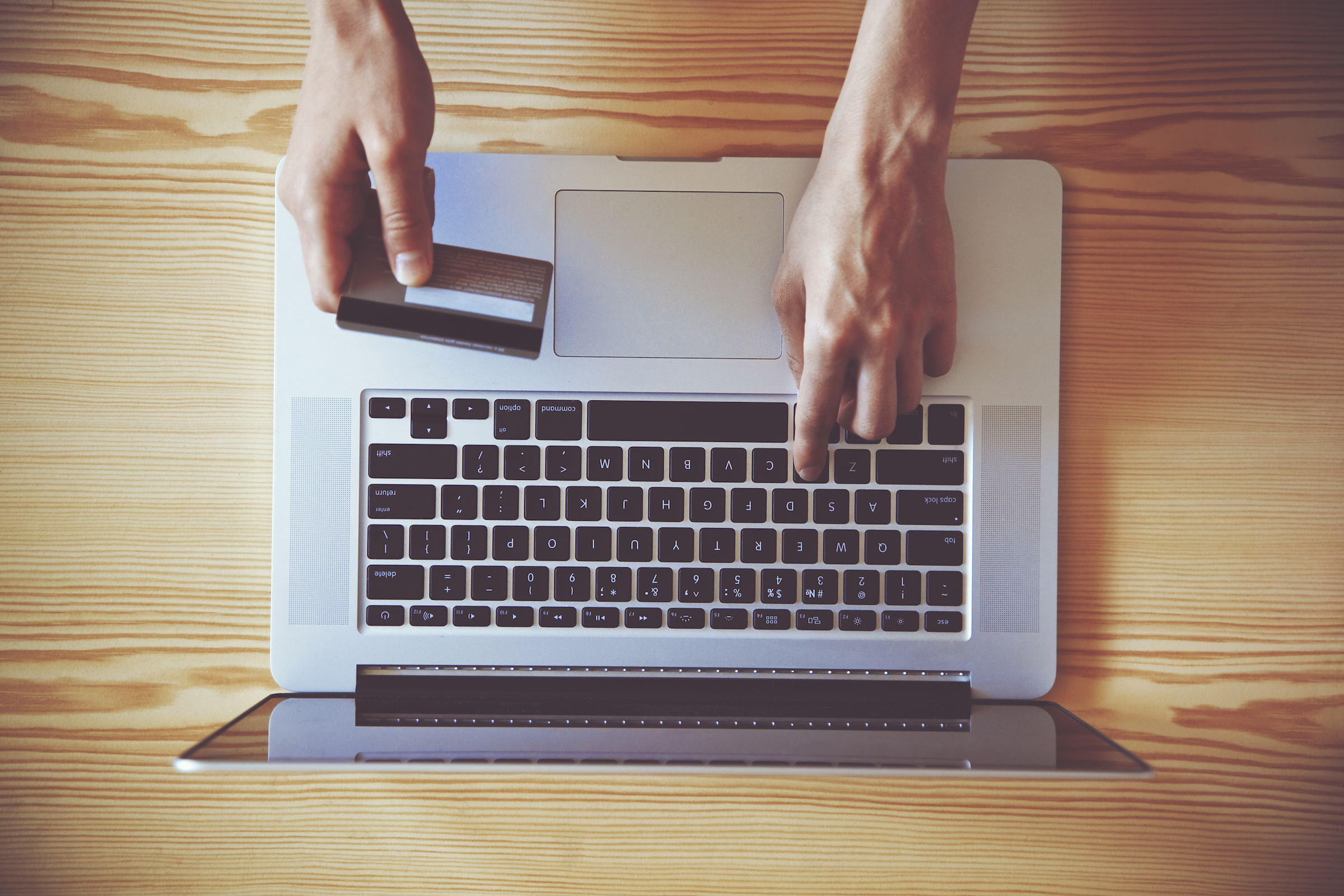 What To Know About Camino Checking Accounts | Camino Federal Credit Union | Bird's eye view of a pair of hands holding credit card and using laptop
