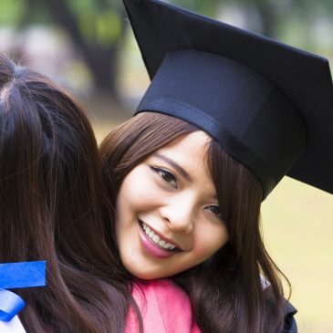 Finance Tips For Graduates | Camino Federal Credit Union | young female graduate hugging her friend at graduation ceremony