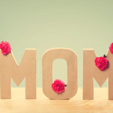 Mother's Day Ideas | Camino Federal Credit Union | Three Dimensional Text That Says Mom with Fresh Carnation Flowers Standing on the Wooden Table with Light Green Background