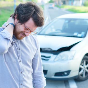 man-rubbing-neck-after-car-crash
