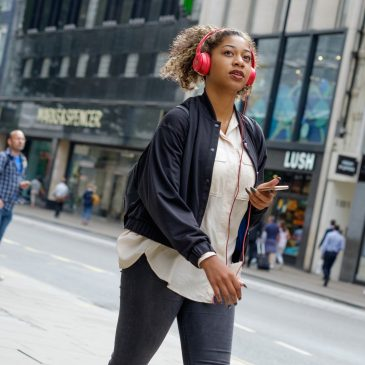 young woman walking through city with headphones and backpack