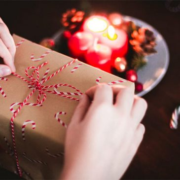 placing bow on wrapped christmas-themed gift