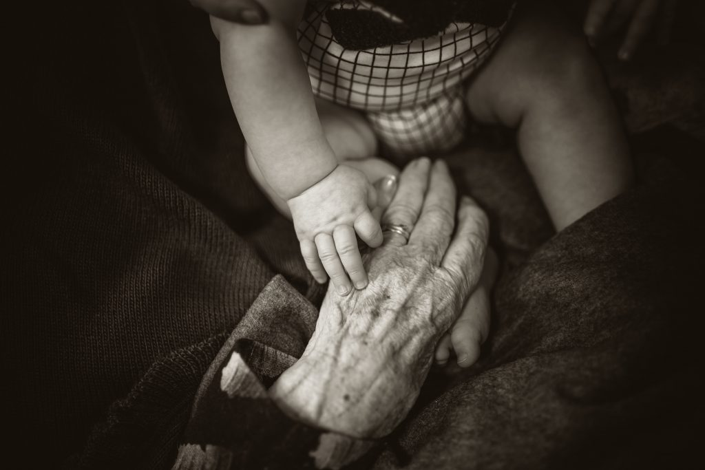baby holding older person's hands