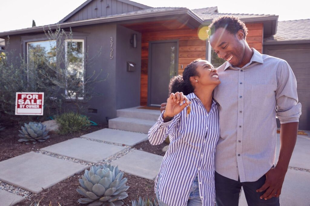"""An African-American couple looks at each other lovingly as they embrace in front of a black ranch-style house with a """"for sale"""" sign."""