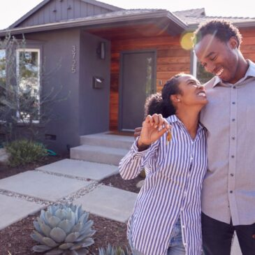 "An African-American couple looks at each other lovingly as they embrace in front of a black ranch-style house with a ""for sale"" sign."