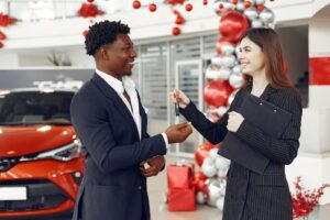 A woman working at a car dealership hands a man car keys as they stand in the dealership in front of a red car