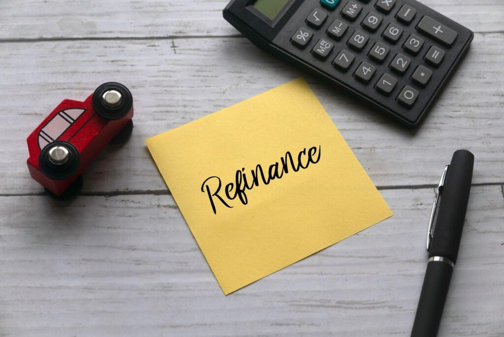"""A yellow sticky note with """"refinance"""" written on it appears on a desk next to a calculator and pen."""