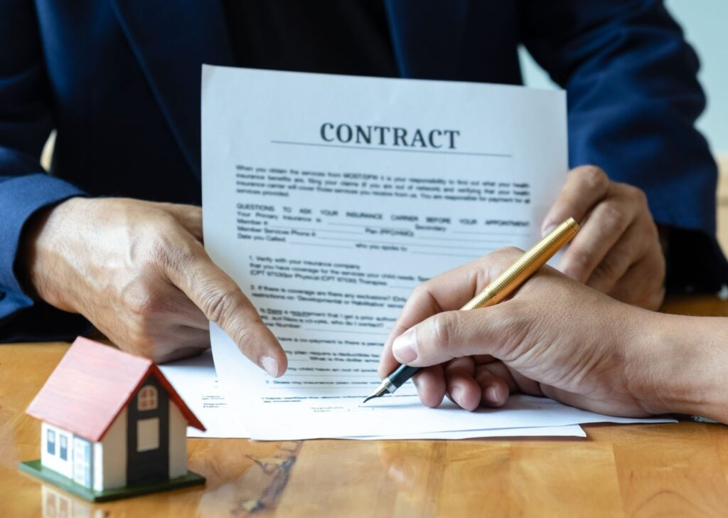 A borrower signs a mortgage contract with a toy house to the side