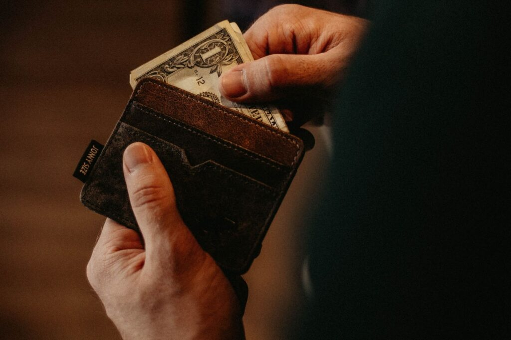 A person pulls a dollar out of his open wallet.