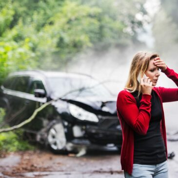 A woman with a hand to her head makes a call next to her wrecked car.