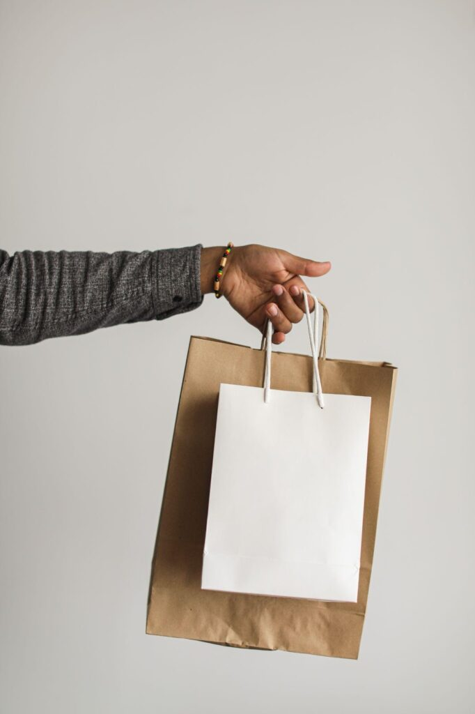 extended arm holds out two shopping bags