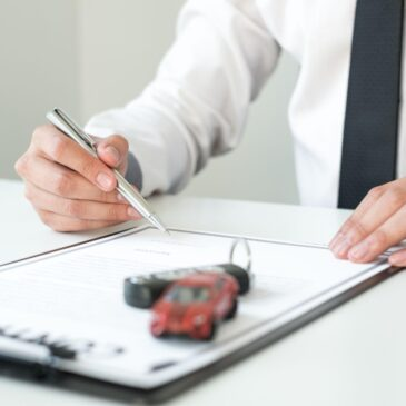 A mini car and keys appear on a clipboard as a man in a suit signs a document