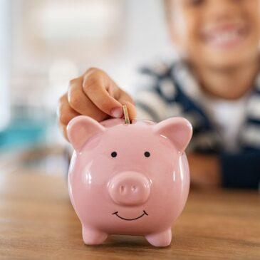 A child puts a coin in a piggy bank