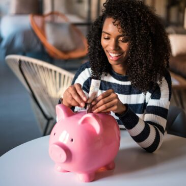 a woman puts a folded dollar bill into a piggy bank