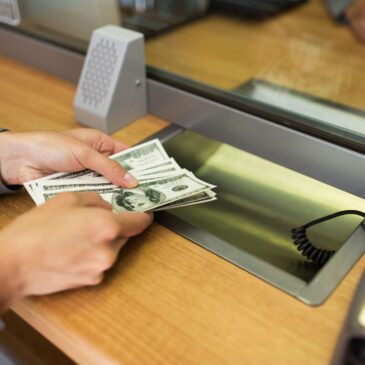 a person at a bank teller window hands over cash